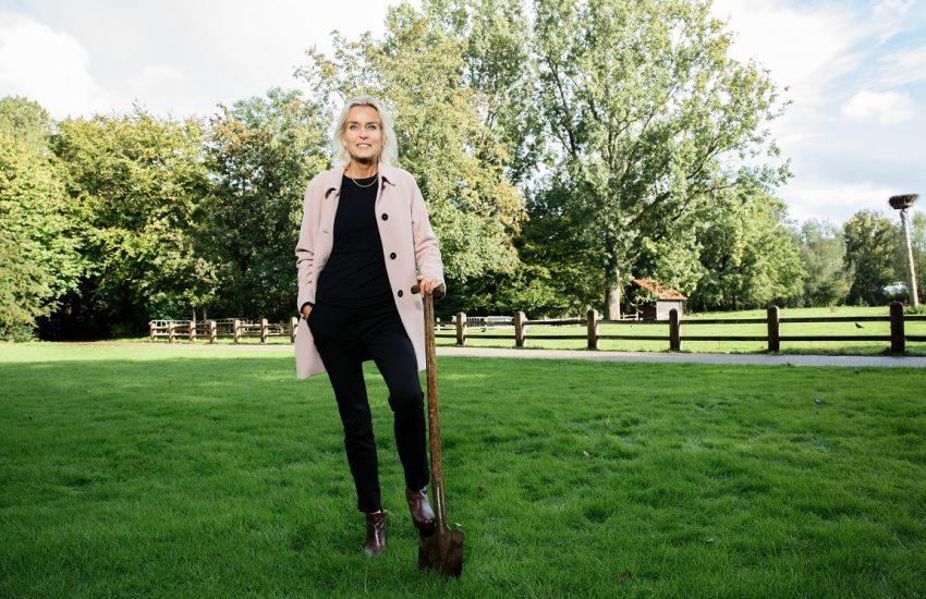 Barbara Baarsma met schep in hand op een grasveld