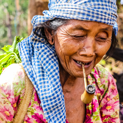 Close-up van een oudere Cambodiaanse vrouw met een pijp in haar mond en een mand met geplukte bosproducten op haar rug.