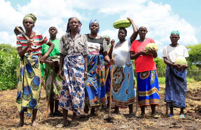 Group of female farmers in the African growth corridors, holding melons and farming equipment.