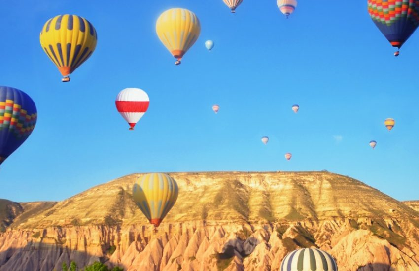 Hot-air balloons in blue sky above mountain range.